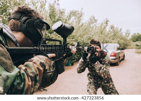 A Photographer Taking A Photo Of A Paintball Player - stock photo