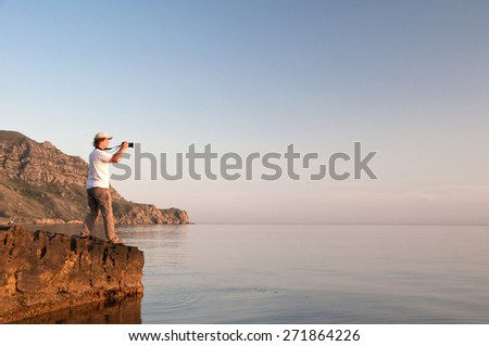 A photographer taking a picture of the sun setting over the ocean. - stock photo
