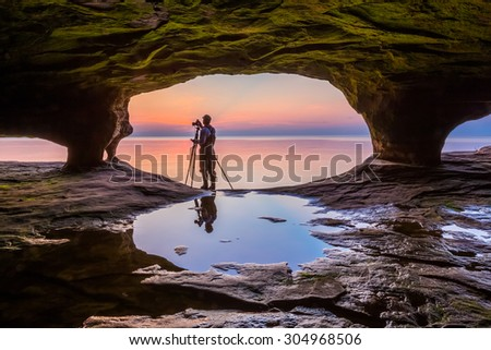 A photographer with tripod, standing in the mouth of a Michigan sea cave, is silhouetted by a colorful sunset over Lake Superior. - stock photo