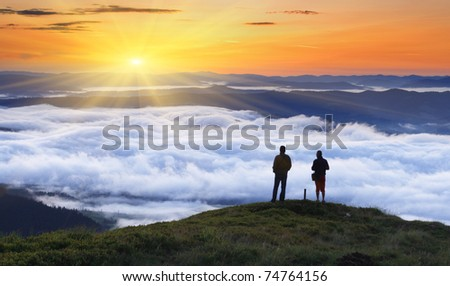 A photographers takes pictures fog from the top of mountain - stock photo