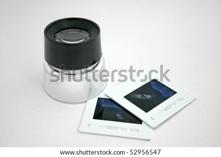 A photographic Lupe and two slide film. - stock photo