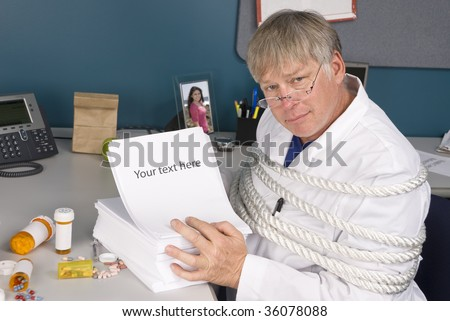 A physician is tied up with a load of bureaucratic paperwork preventing him from doing his job.  Perfect inference for health care reform. - stock photo