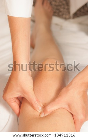 A physio gives myotherapy using trigger points on athlete woman - stock photo