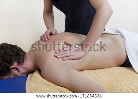 a physiotherapist treats a patient. the back is massaged - stock photo