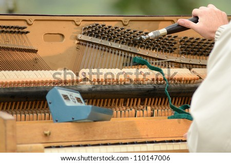 A piano tuner working on an old upright just before a fair concert - stock photo