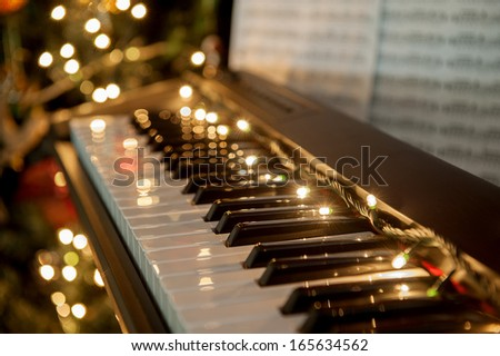 A piano with christmas lights and tree - stock photo