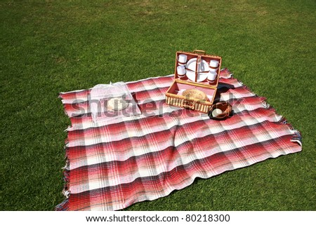 a picnic lunch outdoors in a nice field or park on sunny spring or summer day. picnic includes sandwich, chips, pie, drinks, a blanket and a baseball and glove with a blue sky and green grass. - stock photo