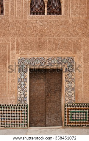 A picture from Alhambra of a wall and wooden door with details of islamic calligraphy - stock photo