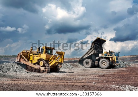 A picture of a big yellow mining truck and bulldozer at worksite - stock photo