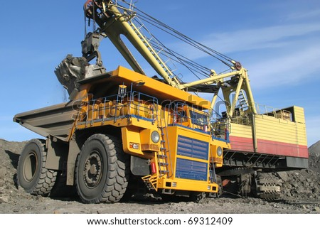 A picture of a big yellow mining truck at worksite - stock photo