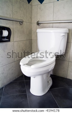 A picture of a commode with no lid and handicap accommodations. - stock photo