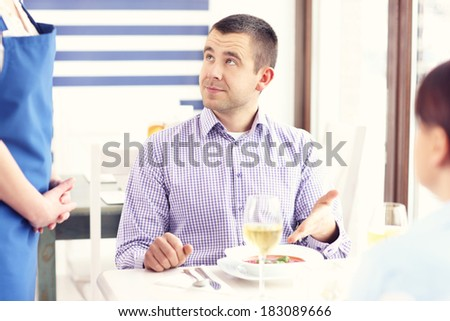 A picture of a customer complaining about the food in a restaurant - stock photo