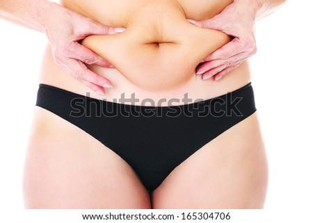 A picture of a fat woman showing her belly over white background - stock photo