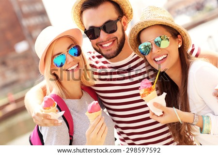 A picture of a group of friends eating ice-cream in front of big wheel in Gdansk - stock photo