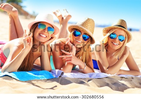 A picture of a group of friends sunbathing on the beach - stock photo