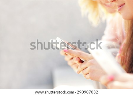A picture of a group of girl friends using smartphones - stock photo