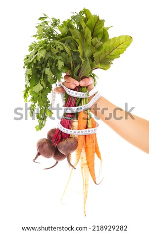 A picture of a hand holding raw carrots and beetroots tied with a tape measure - stock photo