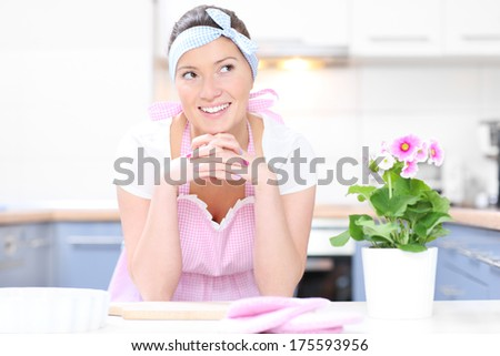A picture of a happy housewife in a pink retro apron posing in the kitchen - stock photo