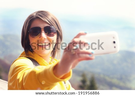 A picture of a happy tourist taking selfie in the mountains - stock photo