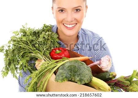 A picture of a happy woman posing with vegetables over white background - stock photo