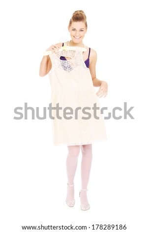 A picture of a happy woman trying on a white dress