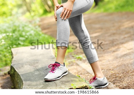 A picture of a jogger having problems with knee in the forest - stock photo