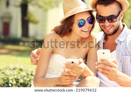 A picture of a joyful couple using smartphones in the park - stock photo