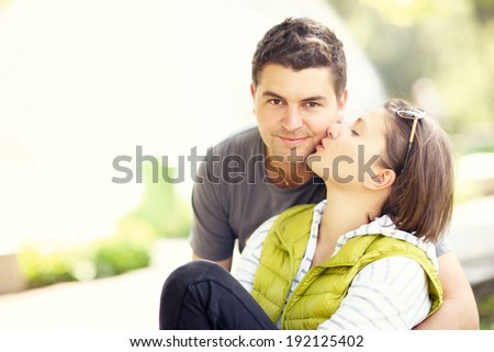 A picture of a kissing couple in the park and copy space on the left - stock photo