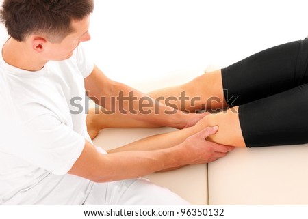 A picture of a physio therapist giving a leg massage over white background - stock photo