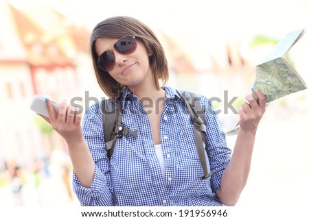 A picture of a stressed woman with a map and cellphone in a town - stock photo