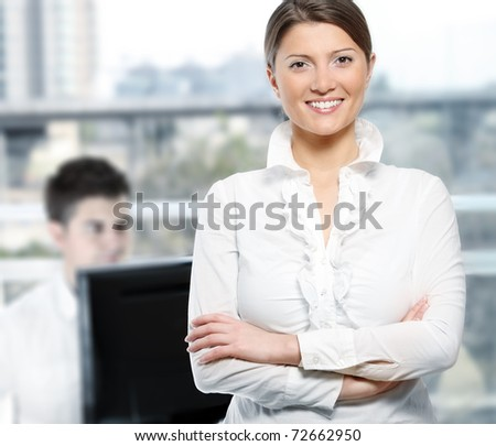 A picture of a successful female leader standing confidently in the office, worker in the background - stock photo