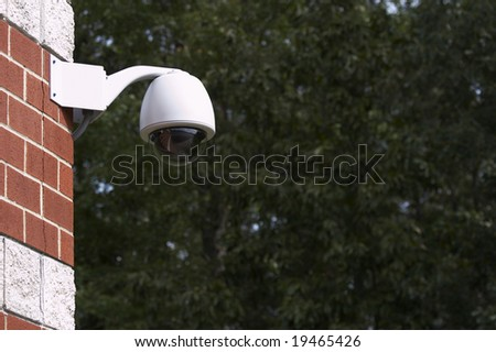 a picture of a surveillance camera on a brick wall - stock photo