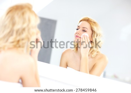 A picture of a woman cleaning face in the bathroom - stock photo