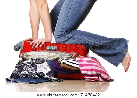 A picture of a woman having problem with packing a suitcase - stock photo