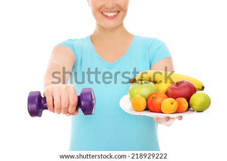 A picture of a woman with fruits and dumb-bells - stock photo