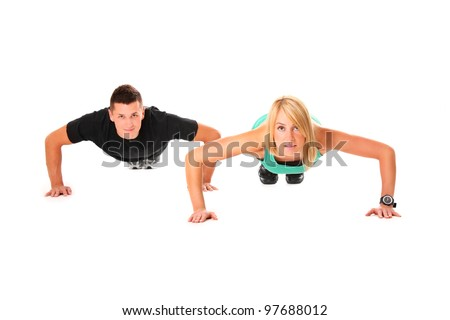A picture of a young couple doing push-ups over white background - stock photo