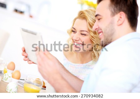 A picture of a young couple eating breakfast in the kitchen and using tablet - stock photo