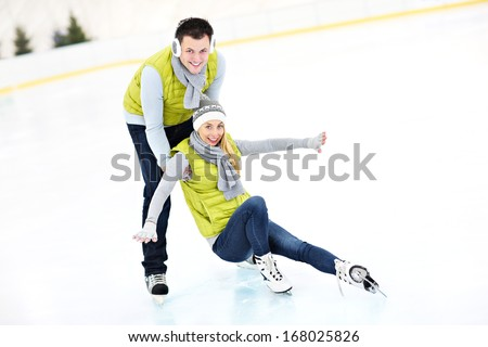 A picture of a young couple ice-skating on a rink - stock photo