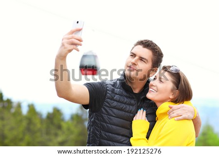 A picture of a young couple taking pictures in the mountains with gondola in the background