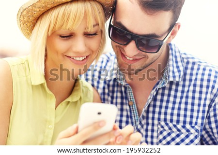 A picture of a young couple using a phone - stock photo