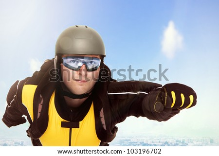A picture of a young parachutist flying over a city in a superman position