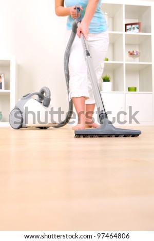 A picture of a young wife hoovering her apartment - stock photo