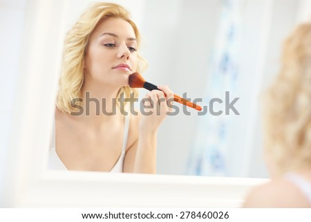 A picture of a young woman applying face powder in the bathroom - stock photo
