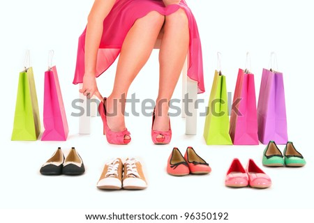 A picture of a young woman trying on new pair of heels over white background - stock photo