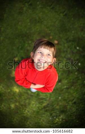 A picture of an adorable little girl standing on the grass and smiling - stock photo