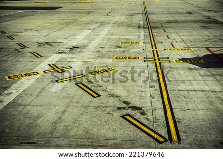 A picture of black and yellow airport markings on concrete runway - stock photo