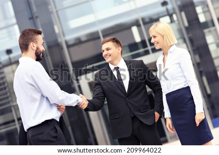 A picture of business people greeting outside modern building - stock photo