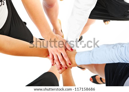 A picture of five businesswomen having their hands joined in unity over white background
