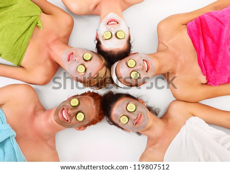 A picture of five girl friends relaxing with facial masks on over white background - stock photo