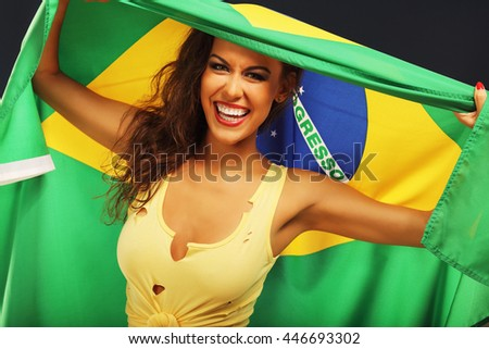 A picture of happy Brazilian fan cheering with flag